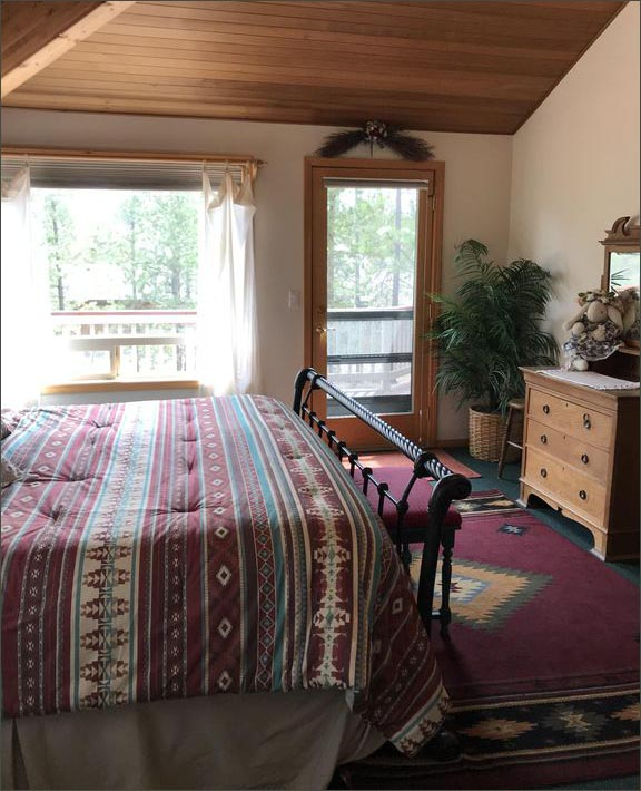 Master bedroom of this private Sunriver home includes a king sized bed and direct access to the upper level, rear facing deck.